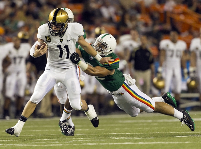 Nov 30, 2013; Honolulu, HI, USA; Hawaii Warriors linebacker Tevita Lataimua (52) tries to pull down Army Black Knights quarterback A.J. Schurr (11) during the third quarter at Aloha Stadium. Mandatory Credit: Marco Garcia-USA TODAY Sports