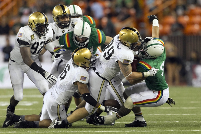 Nov 30, 2013; Honolulu, HI, USA; Army Back Knights defensive end Robert Kough (99) leads the Army defense to stop Hawaii Warriors running back Joey Iosefa (7) during the third quarter at Aloha Stadium. Mandatory Credit: Marco Garcia-USA TODAY Sports