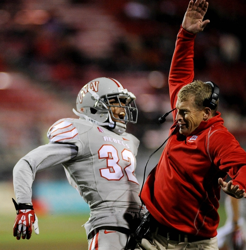 Nov 30, 2013; Las Vegas, NV, USA; UNLV Rebels defensive back Mike Horsey (32) celebrates with Rebels head coach Bobby Hauck after a defensive stop against the San Diego State Aztecs during an NCAA football game at Sam Boyd Stadium. UNLV won the game 45-19. Mandatory Credit: Stephen R. Sylvanie-USA TODAY Sports