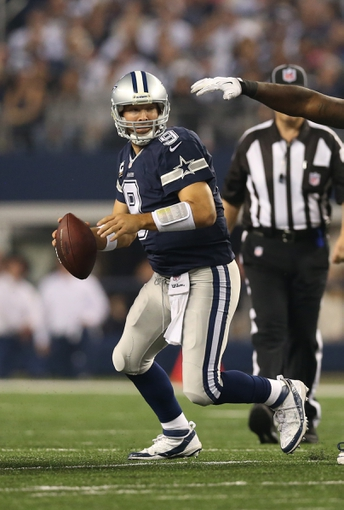Nov 28, 2013; Arlington, TX, USA; Dallas Cowboys quarterback Tony Romo (9) scrambles against the Oakland Raiders during a NFL football game on Thanksgiving at AT&T Stadium. Mandatory Credit: Matthew Emmons-USA TODAY Sports