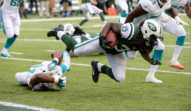 Dec 1, 2013; East Rutherford, NJ, USA; New York Jets running back Chris Ivory (33) is tackled by Miami Dolphins defensive end Cameron Wake (91) in the first half during the game at MetLife Stadium. Mandatory Credit: Robert Deutsch-USA TODAY Sports