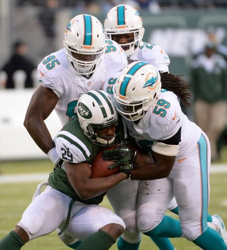 Dec 1, 2013; East Rutherford, NJ, USA; New York Jets running back Bilal Powell (29) is tackled by Miami Dolphins middle linebacker Dannell Ellerbe (59) during the game at MetLife Stadium. Mandatory Credit: Robert Deutsch-USA TODAY Sports