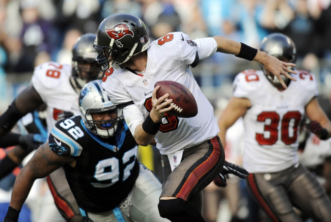 Dec 1, 2013; Charlotte, NC, USA; Tampa Bay Buccaneers quarterback Mike Glennon (8) scrambles away from Carolina Panthers defensive tackle Dwan Edwards (92) during the second half of the game at Bank of America Stadium. Carolina wins 27-6. Mandatory Credit: Sam Sharpe-USA TODAY Sports