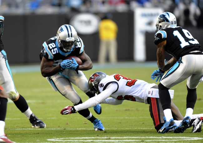 Dec 1, 2013; Charlotte, NC, USA; Carolina Panthers running back Kenjon Barner (25) breaks the tackle of Tampa Bay Buccaneers cornerback Danny Gorrer (36) during the second half of the game at Bank of America Stadium. Carolina wins 27-6. Mandatory Credit: Sam Sharpe-USA TODAY Sports