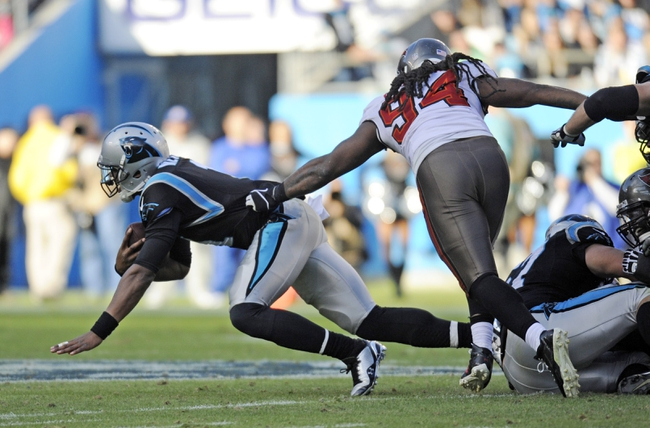 Dec 1, 2013; Charlotte, NC, USA; Carolina Panthers quarterback Cam Newton (1) is stopped by Tampa Bay Buccaneers defensive end Adrian Clayborn (94) during the second half of the game at Bank of America Stadium. Carolina wins 27-6. Mandatory Credit: Sam Sharpe-USA TODAY Sports