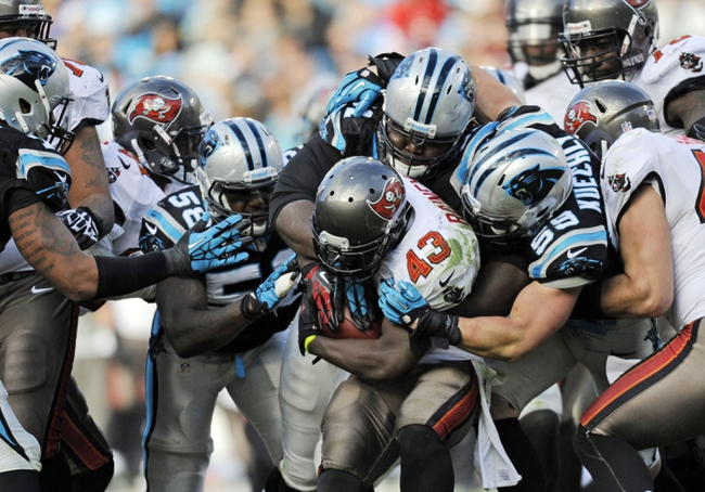 Dec 1, 2013; Charlotte, NC, USA; Tampa Bay Buccaneers running back Bobby Rainey (43) gets stopped by Carolina Panthers linebacker Thomas Davis (58), defensive tackle Colin Cole (91) and linebacker Luke Kuechly (59) during the second half of the game at Bank of America Stadium. Carolina wins 27-6. Mandatory Credit: Sam Sharpe-USA TODAY Sports