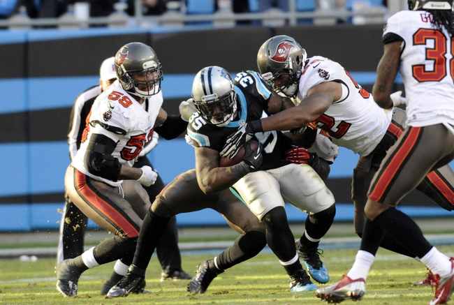 Dec 1, 2013; Charlotte, NC, USA; Carolina Panthers fullback Mike Tolbert (35) runs against Tampa Bay Buccaneers defensive end William Gholston (92) during the second half of the game at Bank of America Stadium. Carolina wins 27-6. Mandatory Credit: Sam Sharpe-USA TODAY Sports