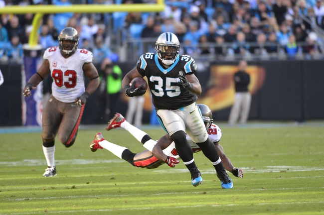Dec 1, 2013; Charlotte, NC, USA; Carolina Panthers fullback Mike Tolbert (35) runs as Tampa Bay Buccaneers defensive tackle Gerald McCoy (93) and cornerback Johnthan Banks (27) defend in the fourth quarter. The Carolina Panthers defeated the Tampa Bay Buccaneers 27-6 at Bank of America Stadium. Mandatory Credit: Bob Donnan-USA TODAY Sports