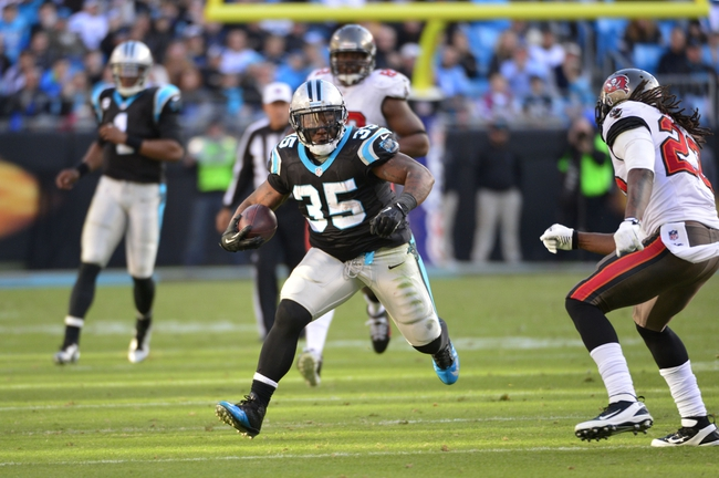 Dec 1, 2013; Charlotte, NC, USA; Carolina Panthers fullback Mike Tolbert (35) runs as Tampa Bay Buccaneers cornerback Johnthan Banks (27) defends in the fourth quarter. The Carolina Panthers defeated the Tampa Bay Buccaneers 27-6 at Bank of America Stadium. Mandatory Credit: Bob Donnan-USA TODAY Sports