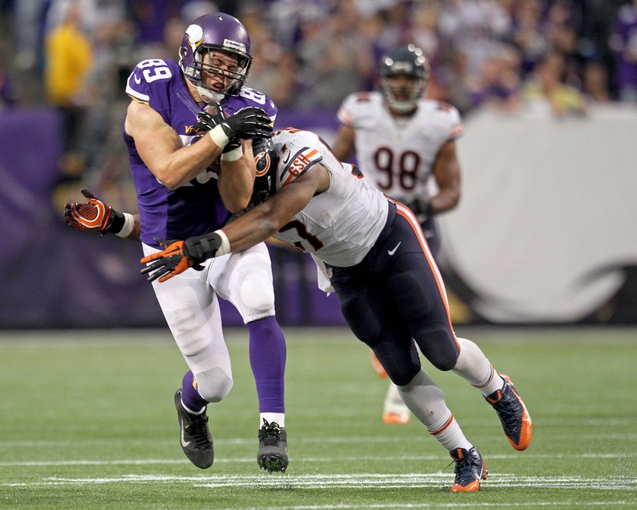 Dec 1, 2013; Minneapolis, MN, USA; Minnesota Vikings tight end John Carlson (89) is tackled by Chicago Bears linebacker Jon Bostic (57) during the fourth quarter at Mall of America Field at H.H.H. Metrodome. The Vikings defeated the Bears 23-20 in overtime. Mandatory Credit: Brace Hemmelgarn-USA TODAY Sports