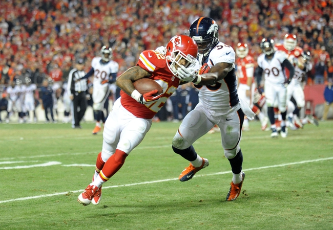 Dec 1, 2013; Kansas City, MO, USA; Kansas City Chiefs wide receiver Dexter McCluster (22) catches a pass as Denver Broncos strong safety Duke Ihenacho (33) attempts the tackle during the second half of the game at Arrowhead Stadium. Denver won 35-28. Mandatory Credit: Denny Medley-USA TODAY Sports