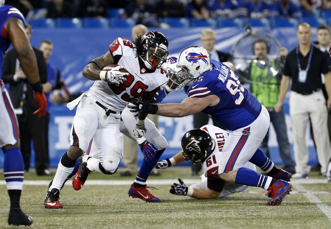 Dec 1, 2013; Toronto, ON, Canada; Buffalo Bills defensive tackle Kyle Williams (95) tackles Atlanta Falcons running back Steven Jackson (39) during the second half at the Rogers Center. Falcons beat the Bills 34-31. Mandatory Credit: Kevin Hoffman-USA TODAY Sports