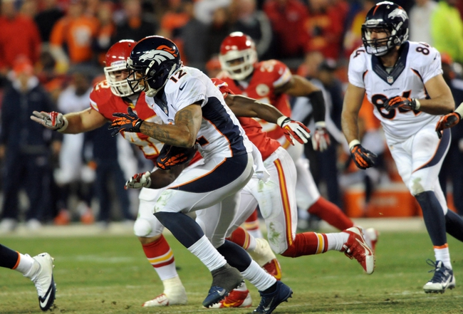 Dec 1, 2013; Kansas City, MO, USA; Denver Broncos wide receiver Andre Caldwell (12) runs the ball as Kansas City Chiefs fullback Anthony Sherman (42) attempts the tackle during the second half of the game at Arrowhead Stadium. Denver won 35-28. Mandatory Credit: Denny Medley-USA TODAY Sports