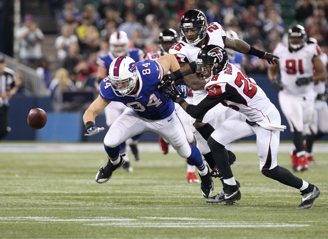 Dec 1, 2013; Toronto, ON, Canada; Atlanta Falcons strong safety William Moore (25) forces a fumble by Buffalo Bills tight end Scott Chandler (84) during overtime at the Rogers Center. Falcons beat the Bills 34 to 31 in overtime.  Mandatory Credit: Timothy T. Ludwig-USA TODAY Sports