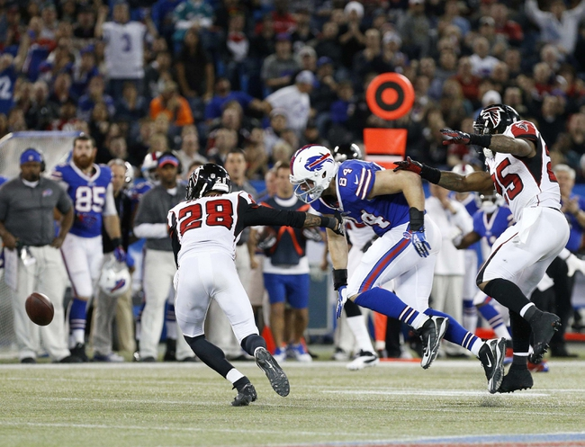 Dec 1, 2013; Toronto, ON, Canada; Buffalo Bills tight end Scott Chandler (84) fumbles the ball after being hit by Atlanta Falcons strong safety William Moore (25) during OT at the Rogers Center. Falcons beat the Bills 34-31. Mandatory Credit: Kevin Hoffman-USA TODAY Sports