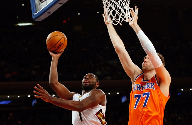 Dec 1, 2013; New York, NY, USA;  New Orleans Pelicans point guard Tyreke Evans (1) shoots as New York Knicks power forward Andrea Bargnani (77) defends during the fourth quarter at Madison Square Garden. New Orleans Pelicans won 103-99.  Mandatory Credit: Anthony Gruppuso-USA TODAY Sports
