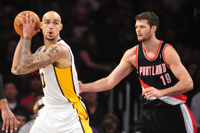 December 1, 2013; Los Angeles, CA, USA; Los Angeles Lakers center Robert Sacre (50) controls the ball against the defense of Portland Trail Blazers center Joel Freeland (19) during the first half at Staples Center. Mandatory Credit: Gary A. Vasquez-USA TODAY Sports