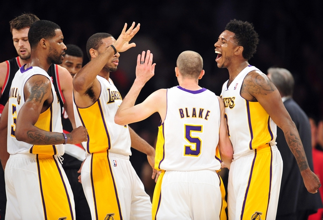 December 1, 2013; Los Angeles, CA, USA; Los Angeles Lakers small forward Nick Young (0) celebrates after point guard Steve Blake (5) scores a three point basket to end the first quarter against the Portland Trail Blazers at Staples Center. Mandatory Credit: Gary A. Vasquez-USA TODAY Sports