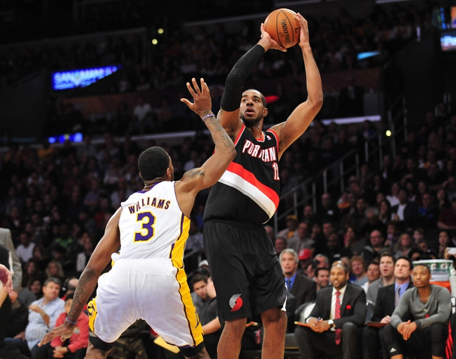 December 1, 2013; Los Angeles, CA, USA; Portland Trail Blazers power forward LaMarcus Aldridge (12) shoots a basket against the defense of Los Angeles Lakers power forward Shawne Williams (3) during the first half at Staples Center. Mandatory Credit: Gary A. Vasquez-USA TODAY Sports