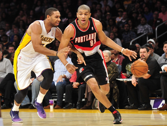 December 1, 2013; Los Angeles, CA, USA; Portland Trail Blazers small forward Nicolas Batum (88) moves the ball against the defense of Los Angeles Lakers small forward Xavier Henry (7) during the first half at Staples Center. Mandatory Credit: Gary A. Vasquez-USA TODAY Sports