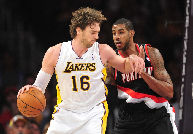 December 1, 2013; Los Angeles, CA, USA; Los Angeles Lakers center Pau Gasol (16) moves the ball against the defense of Portland Trail Blazers power forward LaMarcus Aldridge (12) during the first half at Staples Center. Mandatory Credit: Gary A. Vasquez-USA TODAY Sports