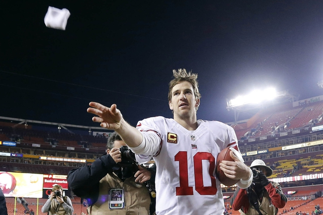 Dec 1, 2013; Landover, MD, USA;  New York Giants quarterback Eli Manning (10) throws a wrist band into the stands after the Giants' game against the Washington Redskins at FedEx Field. The Giants won 24-17. Mandatory Credit: Geoff Burke-USA TODAY Sports