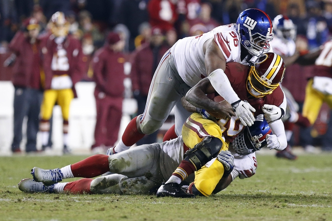 Dec 1, 2013; Landover, MD, USA;  Washington Redskins quarterback Robert Griffin III (10) is sacked by New York Giants defensive tackle Johnathan Hankins (96) and Giants defensive end Justin Tuck (91) in the third quarter at FedEx Field. The Giants won 24-17. Mandatory Credit: Geoff Burke-USA TODAY Sports