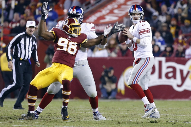 Dec 1, 2013; Landover, MD, USA;  New York Giants quarterback Eli Manning (10) prepares to throw the ball under pressure from Washington Redskins outside linebacker Brian Orakpo (98) in the fourth quarter at FedEx Field. The Giants won 24-17. Mandatory Credit: Geoff Burke-USA TODAY Sports