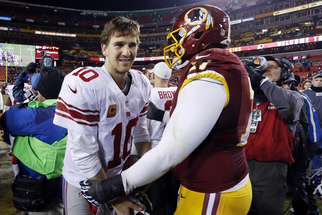 Dec 1, 2013; Landover, MD, USA; New York Giants quarterback Eli Manning (10) shakes hands with Washington Redskins tackle Trent Williams (71) after their game at FedEx Field. The Giants won 24-17. Mandatory Credit: Geoff Burke-USA TODAY Sports
