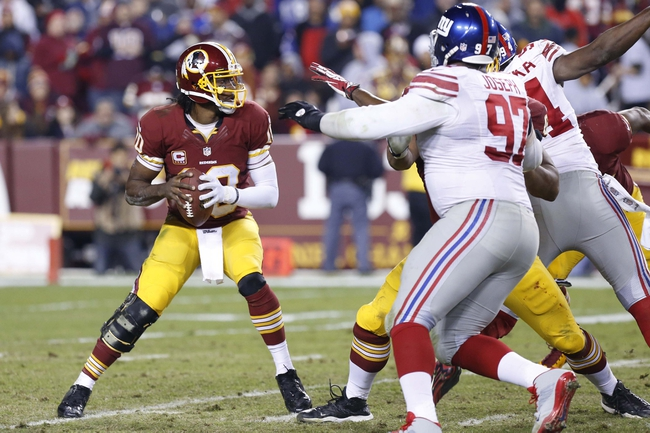Dec 1, 2013; Landover, MD, USA;  Washington Redskins quarterback Robert Griffin III (10) prepares to throw the ball as New York Giants defensive end Mathias Kiwanuka (94) and Giants defensive tackle Linval Joseph (97) defend in the fourth quarter at FedEx Field. The Giants won 24-17. Mandatory Credit: Geoff Burke-USA TODAY Sports