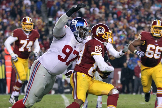 Dec 1, 2013; Landover, MD, USA; Washington Redskins wide receiver Santana Moss (89) runs with the ball as New York Giants defensive tackle Linval Joseph (97) attempts to tackle in the fourth quarter at FedEx Field. The Giants won 24-17. Mandatory Credit: Geoff Burke-USA TODAY Sports