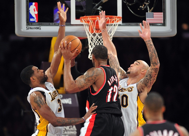 December 1, 2013; Los Angeles, CA, USA; Los Angeles Lakers power forward Shawne Williams (3) and center Robert Sacre (50) defend against Portland Trail Blazers power forward LaMarcus Aldridge (12) during the second half at Staples Center. Mandatory Credit: Gary A. Vasquez-USA TODAY Sports