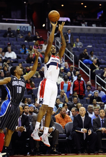 Dec 2, 2013; Washington, DC, USA; Washington Wizards small forward Trevor Ariza (1) attempts a shot as Orlando Magic point guard Ronnie Price (10) defends during the first half at the Verizon Center. Mandatory Credit: Brad Mills-USA TODAY Sports
