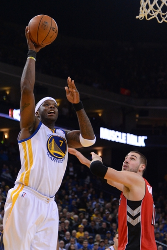 December 3, 2013; Oakland, CA, USA; Golden State Warriors center Jermaine O'Neal (7) shoots the basketball against Toronto Raptors center Jonas Valanciunas (17) during the fourth quarter at Oracle Arena. The Warriors defeated the Raptors 112-103. Mandatory Credit: Kyle Terada-USA TODAY Sports