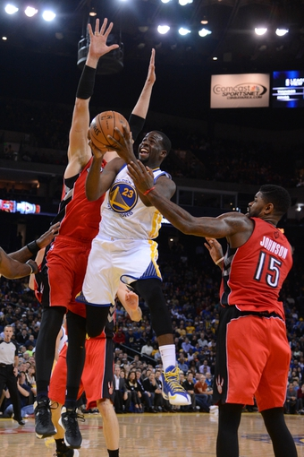 December 3, 2013; Oakland, CA, USA; Golden State Warriors small forward Draymond Green (23) shoots the basketball against Toronto Raptors power forward Amir Johnson (15) during the fourth quarter at Oracle Arena. The Warriors defeated the Raptors 112-103. Mandatory Credit: Kyle Terada-USA TODAY Sports