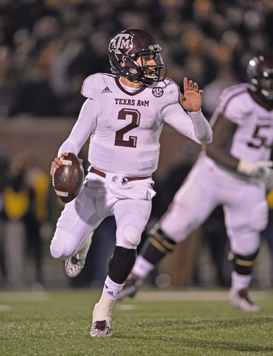 Nov 30, 2013; Columbia, MO, USA; Texas A&M Aggies quarterback Johnny Manziel (2) rolls out against the Missouri Tigers during the second half at Faurot Field. Mandatory Credit: Peter G. Aiken-USA TODAY Sports