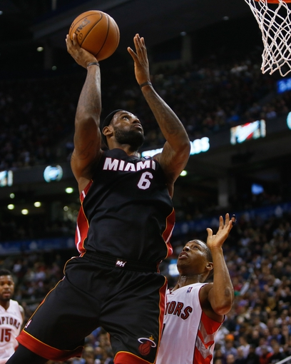 Nov 29, 2013; Toronto, Ontario, CAN; Miami Heat forward LeBron James (6) goes up to make a basket as Toronto Raptors guard Kyle Lowry (7) looks on at the Air Canada Centre. Miami defeated Toronto 90-83. Mandatory Credit: John E. Sokolowski-USA TODAY Sports