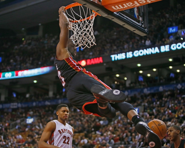 Nov 29, 2013; Toronto, Ontario, CAN; Miami Heat guard Dwyane Wade (3) hangs off the basket after dunking the ball as Toronto Raptors forward Rudy Gay (22) looks on at the Air Canada Centre. Miami defeated Toronto 90-83. Mandatory Credit: John E. Sokolowski-USA TODAY Sports