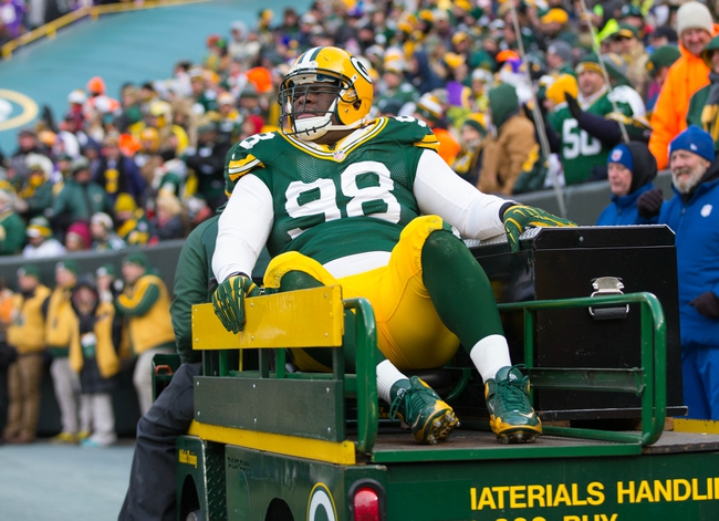 Nov 24, 2013; Green Bay, WI, USA; Green Bay Packers defensive end C.J. Wilson (98) is carted from the field during the game against the Minnesota Vikings at Lambeau Field.  The Vikings and Packers tied 26-26.  Mandatory Credit: Jeff Hanisch-USA TODAY Sports