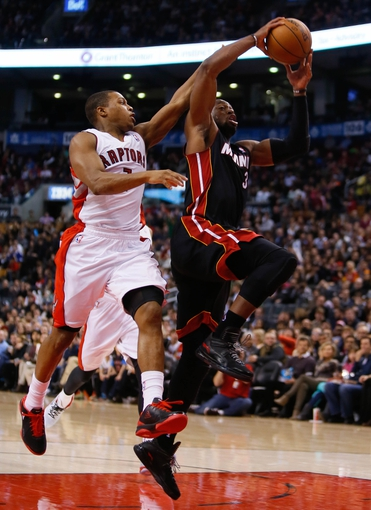 Nov 29, 2013; Toronto, Ontario, CAN; Toronto Raptors guard Kyle Lowry (7) defends against Miami Heat guard Dwyane Wade (3) at the Air Canada Centre. Miami defeated Toronto 90-83. Mandatory Credit: John E. Sokolowski-USA TODAY Sports