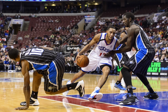 Dec 3, 2013; Philadelphia, PA, USA; Philadelphia 76ers guard Evan Turner (12) is defended by Orlando Magic forward Andrew Nicholson (44) during overtime at the Wells Fargo Center. The Sixers defeated the Magic 126-125 in double overtime. Mandatory Credit: Howard Smith-USA TODAY Sports