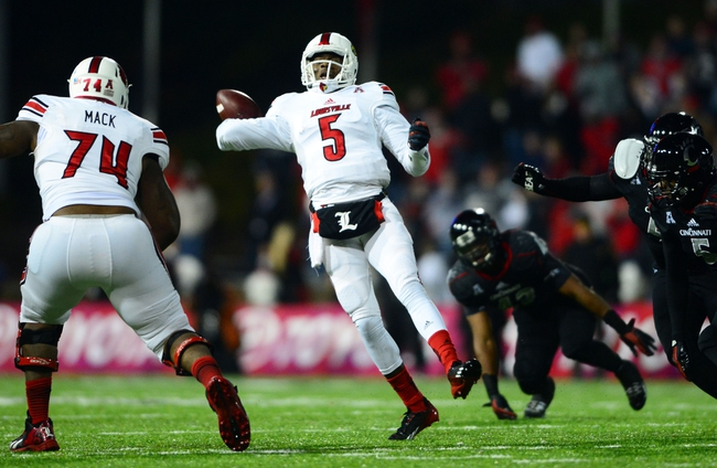 Dec 5, 2013; Cincinnati, OH, USA; Louisville Cardinals quarterback Teddy Bridgewater (5) scrambles out of the pocket and throws a pass for a touchdown during the fourth quarter against the Cincinnati Bearcats at Nippert Stadium. Mandatory Credit: Andrew Weber-USA TODAY Sports