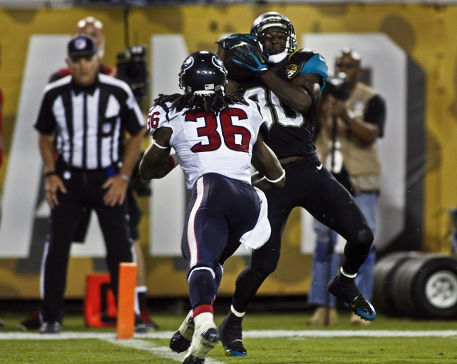 Dec 5, 2013; Jacksonville, FL, USA; Jacksonville Jaguars running back Jordan Todman (30) catches a 21-yard touchdown pass thrown by wide receiver Ace Sanders (not pictured) as Houston Texans strong safety D.J. Swearinger (36) defends in the third quarter at EverBank Field. Mandatory Credit: Phil Sears-USA TODAY Sports