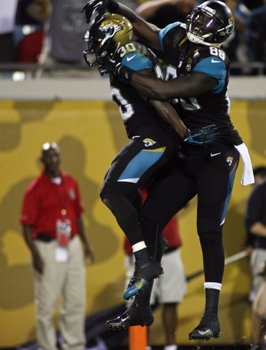 Dec 5, 2013; Jacksonville, FL, USA; Jacksonville Jaguars running back Jordan Todman (30) celebrates with tight end Danny Noble (88) after catching a 21-yard touchdown pass thrown by wide receiver Ace Sanders (not pictured) in the third quarter against the Houston Texans at EverBank Field. Mandatory Credit: Phil Sears-USA TODAY Sports