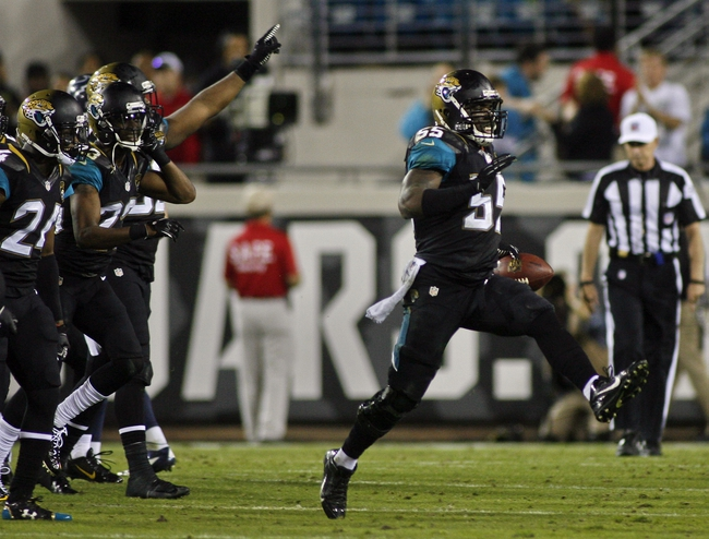 Dec 5, 2013; Jacksonville, FL, USA; Jacksonville Jaguars linebacker Geno Hayes (55) celebrates after making an interception in the final three minutes of the fourth quarter against the Houston Texans at EverBank Field. The Jacksonville Jaguars best the Houston Texans 27-20. Mandatory Credit: Phil Sears-USA TODAY Sports