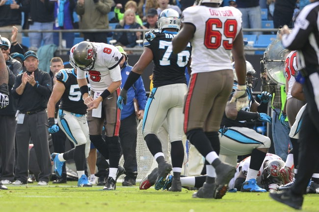 Dec 1, 2013; Charlotte, NC, USA; Tampa Bay Buccaneers quarterback Mike Glennon (8) reacts after fumbling the ball as tackle Demar Dotson (69) and Carolina Panthers defensive end Greg Hardy (76) looks on in the second quarter at Bank of America Stadium. Mandatory Credit: Bob Donnan-USA TODAY Sports