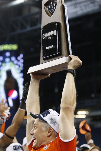Dec 6, 2013; Detroit, MI, USA; Bowling Green Falcons head coach Dave Clawson celebrates with the trophy after winning the Mac Championship game against the Northern Illinois Huskies 47-27 at Ford Field. Mandatory Credit: Rick Osentoski-USA TODAY Sports