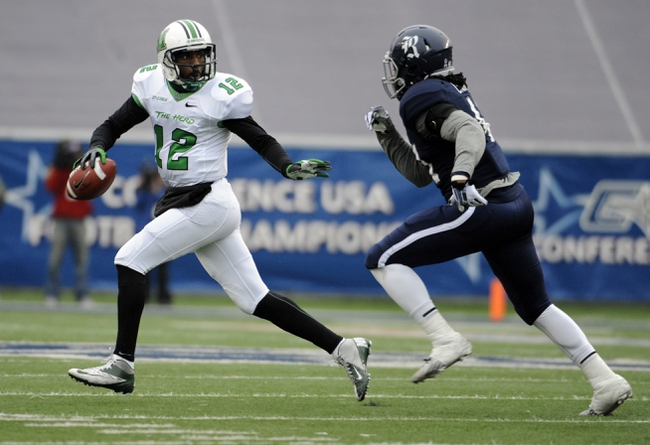 Dec 7, 2013; Houston, TX, USA; Marshall Thundering Herd quarterback Rakeem Cato (12) is chased by Rice Owls linebacker Alex Lyons (41) during the first half at Rice Stadium. Mandatory Credit: Brendan Maloney-USA TODAY Sports