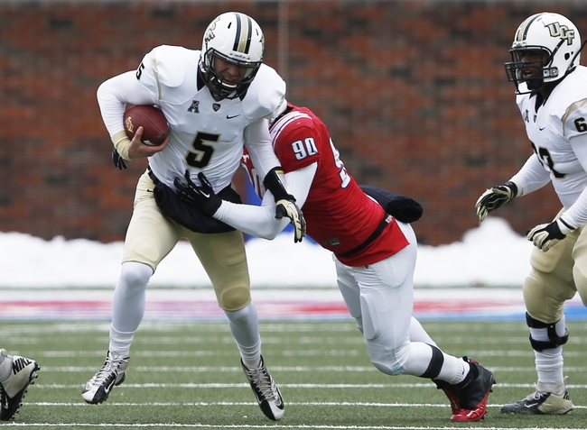 Dec 7, 2013; Dallas, TX, USA; UCF Knights quarterback Blake Bortles (5) evades the tackle by Southern Methodist Mustangs defensive end Zach Wood (90) during the first half of an NCAA football game at Gerald J. Ford Stadium. Mandatory Credit: Jim Cowsert-USA TODAY Sports