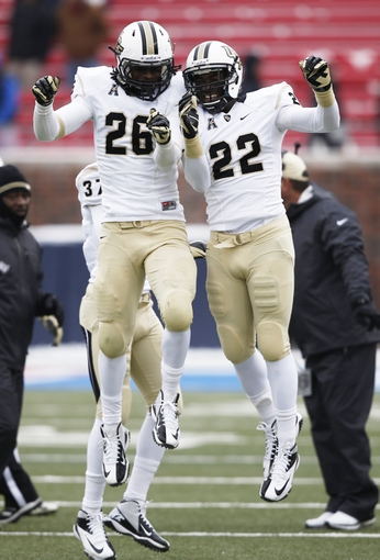 Dec 7, 2013; Dallas, TX, USA; UCF Knights defensive back Clayton Geathers (26) celebrates his interception with UCF Knights defensive back Jared Henry (22) against the Southern Methodist Mustangs during the second half of an NCAA football game at Gerald J. Ford Stadium. UCF Knights won 17-13. Mandatory Credit: Jim Cowsert-USA TODAY Sports
